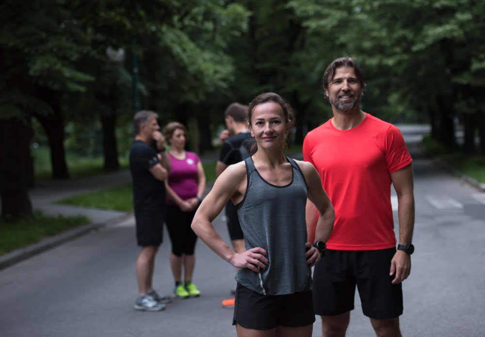 Fit man and woman standing in front of running group