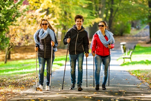 3 people nordic walking on a park path