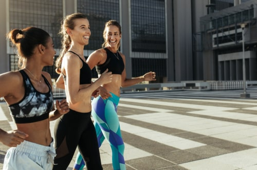 3 women walking for fitness on a city street